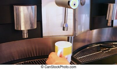 water being poured in mug from machine by button pressing