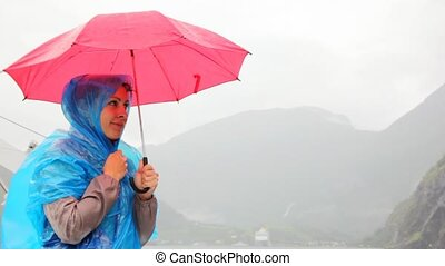 woman under umbrella freezes against rocky landscapes -...