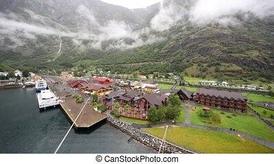 small port with houses and railway in hollow among mountains...