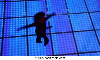 Woman spins in dance at dark discotheque with illuminated floor