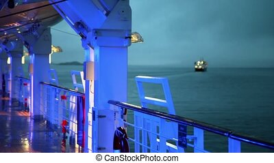 Illumination on deck of ship which floats at sea where other...