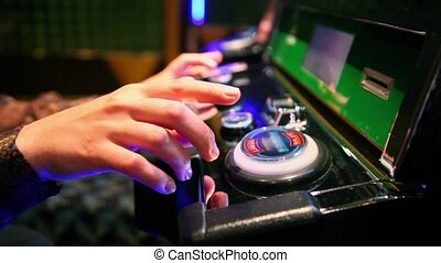 Woman pushes buttons on play machine in casino, only hands...
