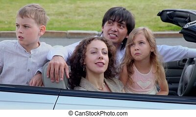 Parents and two kids sit in cabriolet and watch upward