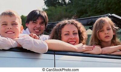 Family sit in cabriolet and smile at sunny summer day