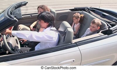Family ride in cabriolet at sunny summer day, around motion