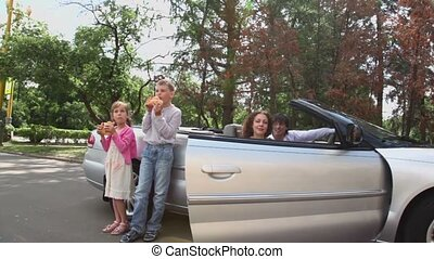 Two kids eats bread near cabriolet, parents sit in cabriolet