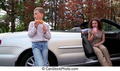 Boy stand and eats near cabriolet, his parents drink in car