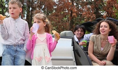 kids eats bread and drink water, parents sit in cabriolet -...