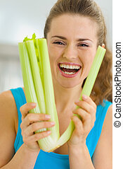 Smiling young woman holding celery