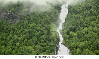 Waterfall and river among forest on mountain at shore of fiord