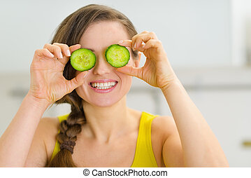 Smiling young woman holding slices of cucumber in front of...
