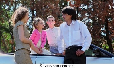 Parents talk with their kids in cabriolet at sunny summer...