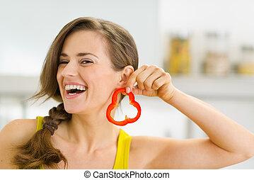 Feliz, jovem, mulher, usando, fatia, sino, pimenta, Brinco