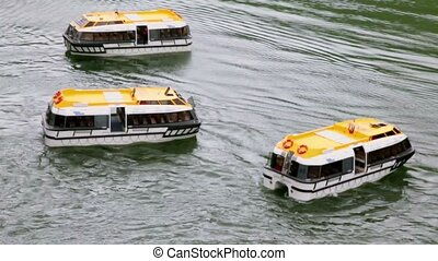 Three empty passengers transport vessels swing on water...