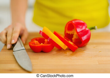Closeup on red bell pepper with yellow slice on cutting...