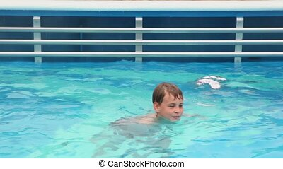 Boy swims in pool from which vapor rises up
