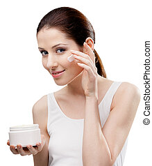 Woman putting on cream from container on face, isolated on...
