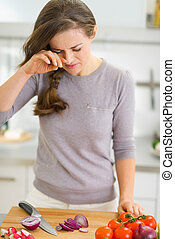 Young housewife crying while cutting onion
