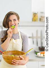 Happy young housewife tasting slice of cucumber from...