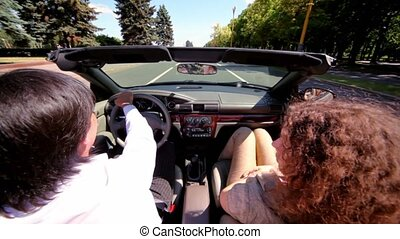 Man and woman sit in cabriolet and ride by road at summer...