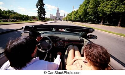 Man and woman ride in cabriolet on way at day