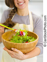 Closeup on fresh vegetable salad in hand of housewife