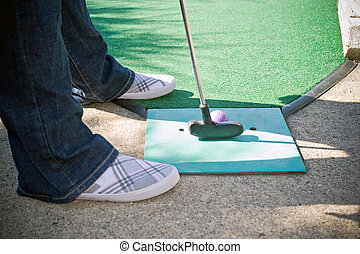 Mini Golfer - A person getting ready to putt while playing...
