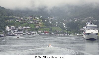 Rescue boat float on fiord to village and huge liner near shore