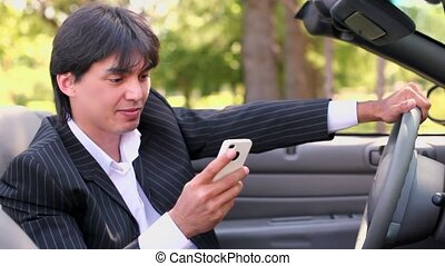 Caucasian male sits in cabriolet and talks phone at summer...