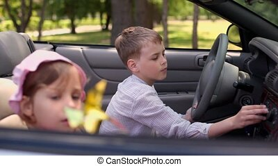 kids sit in cabriolet, girl blows toy and brother push buttons