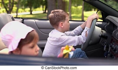 Two kids sit in cabriolet, girl plays toy and her brother holds driver wheel, focus on boy