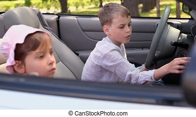 Two kids boy and girl sit in cabriolet at summer day