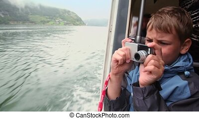 Boy makes photo from rescue boat which floats on fjord with...