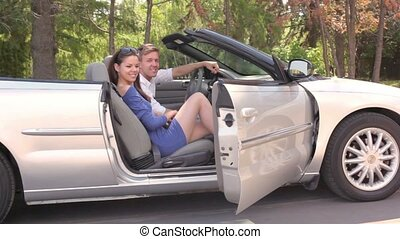 Young couple sit in cabriolet and girl closes door at sunny...