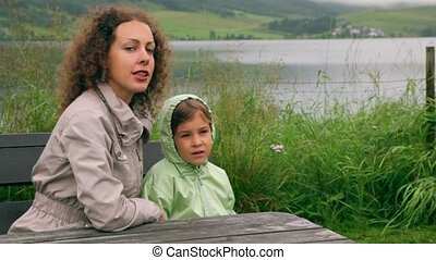 Mother with her little daughter sit at background of lake...