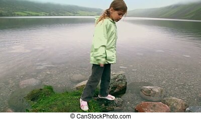 Little girl checks stone in water of fiord with mountains