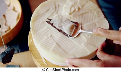 Hand cut cheese with special tool, closeup view in dark