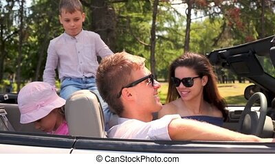 Students in sunglasses and two kids sit in cabriolet at...