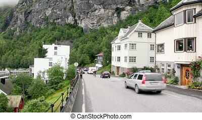 Several cars ride on street of mountain village at spring...
