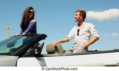 Girl in sunglasses stand in cabriolet, boyfriend sit near