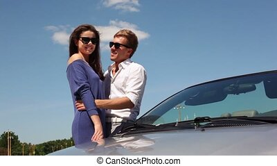 Boy leans on cabriolet and embrace girl, both wear...