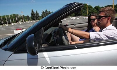 Young couple sit in cabriolet and ride by road at sunny day...