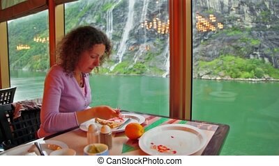 Woman sits at table and eats in front of window, waterfall...