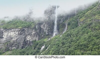 Waterfall from under clouds at mountain among forest in...