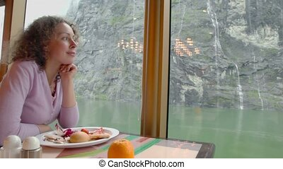 Woman sits at table with food and watch waterfall on mountain