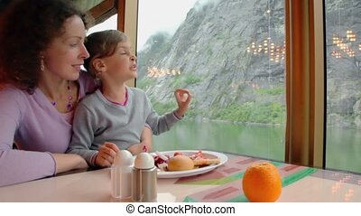 Mother and daughter sit at table with food and watch...