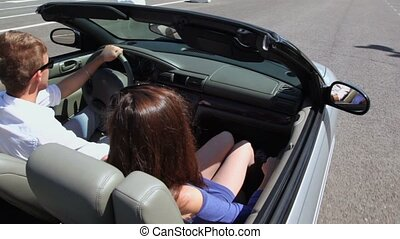 Young couple ride in cabriolet by road, view from above