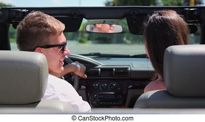 Young couple ride in cabriolet and turn at sunny summer day