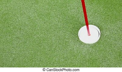 Small white ball passes by near flag in minigolf on green...