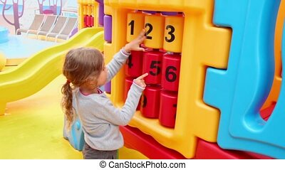 Little girl play huge toy with digits at playground